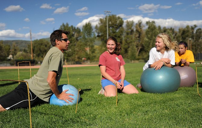 Steamboat Springs Winter Sports Club Alpine coach Rob Worrell demonstrates how not to work out for Olivia Rudolph, from left, Kate Cooper and Miranda Salky.  The Winter Sports Club went through dryland training exercises Friday.  The first step toward being in proper shape for ski season, local fitness experts said, is establishing a good fitness base.