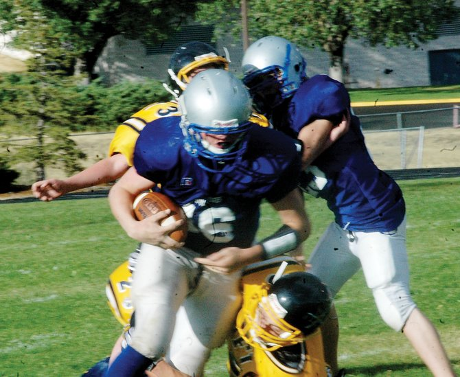 Bubba Ivers, center, powers his way through Rifle High School's boys freshman team defenders. Ivers, the Moffat County High School boys freshman team quarterback, paced his team in the 50-0 rout of the Bears.