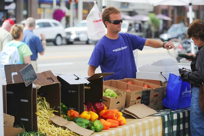 Sweet Pea Market employee Adam Gray mans the cash register at the business' Mainstreet Farmers Market booth Saturday. The event ended this weekend.
