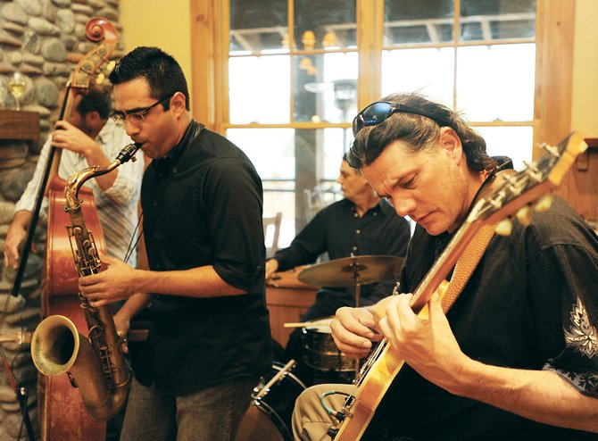 Jon Ridnell, of the Jon Ridnell Quartet, of Denver, plays the guitar while Serafin Sanchez plays the saxophone Sunday at Partners in Routt County's third annual Java & Jazz fundraiser at the Lake Catamount clubhouse.