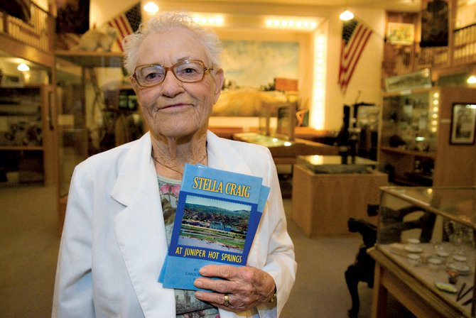 "Stella Craig stands in the Museum of Northwest Colorado with her recently published book, ""Stella Craig at Juniper Hot Springs."" The book is a history of Juniper Hot Springs, located west of Craig, which Stella owned and operated for 45 years."