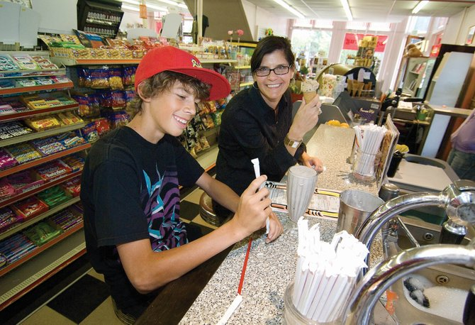 Dane Parke, left, and his mom, Randee Stapp, stopped by the soda fountain at Lyon's Corner Drug on Monday afternoon for a sweet treat. With a 9.1 percent decrease in sales tax collections, the downtown area of the city fared much better than others. Sales tax collections declined 18.2 percent citywide.