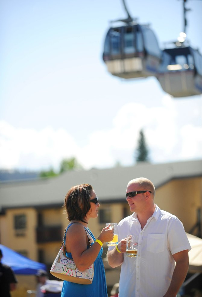 Brooke Jones and Tim Huff, of Grand Junction, enjoy their beers Saturday during OktoberWest at the base of Steamboat Ski Area.