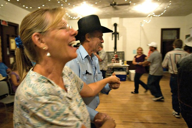 "Connie Strasheim, left, and Norm Culverwell dance to ""Oh, Johnny,"" along with others attending the fall hoedown Saturday at Lodore Hall in Browns Park. About 30 people jumped into the circle to dance with family and friends at the event sponsored by Browns Hole Homemakers Club."