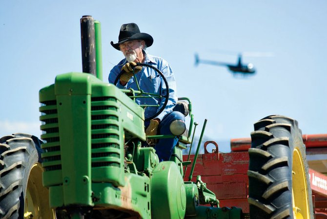 "Gonk Jacobs rides his 1950 ""A"" John Deere tractor Saturday during the antique tractor pull at the 11th annual Sheep Wagon Days at Wyman Museum. The event was part of a series of events throughout the day, including helicopter rides and celebrating the area's sheep ranching heritage."