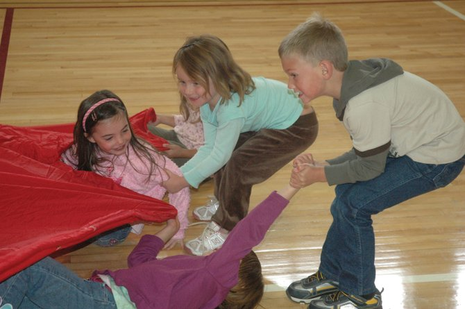 "South Routt Elementary School kindergartners Jed Kirby, counterclockwise from right, and Erika Sjoblom, rescue classmates Marissa Martindale and Sophia Benjamin during a game of ""Shark Attack"" during physical education class Monday. The gymnasium reopened Monday after it had undergone renovations to repair damage to the roof after a June lightning strike."