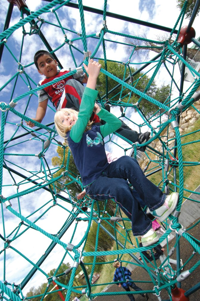 Kindergartners Lilly Price, front, and Luis Simon play on the climbing web at Soda Creek Elementary School Wednesday afternoon. The playground, along with the new playground at Strawberry Park, will be dedicated during a ceremony at 5:30 p.m. today at Strawberry Park.