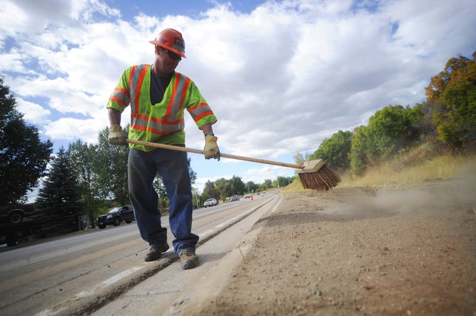 Colorado Department of Transportation maintenance worker Dan O'Connor, of Steamboat Springs, sweeps the curb along U.S. Highway 40 just west of 13th Street during a ditch maintenance project. CDOT workers locally are among those who will be affected by statewide budget shortfalls.