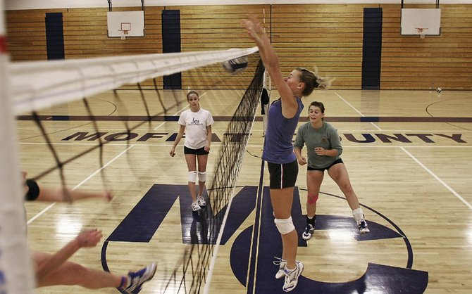 Lauren Roberts, center, and the Moffat County High School volleyball team work on a blocking drill during Wednesday's practice. The Bulldogs play host to the Steamboat Springs High School Sailors for a rivalry match at 6:30 p.m. today.