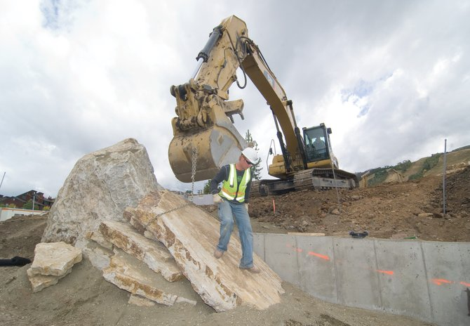 Brady Meier, of Duckels Construction, climbs off a sandstone slab after attaching a chain. The heavy slab was being moved into position by an excavator operated by Derrick Duckels and will be part of an outdoor gathering place near the Burgess Creek diversion.