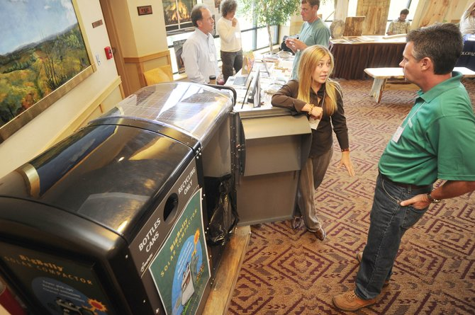 Jeff Machado, of Premier Building Systems, talks Friday with Carissa Huster, of All Around Recreation, about a solar powered trash compactor her company sells during the Sustainability Summit held at the Steamboat Grand Resort Hotel.