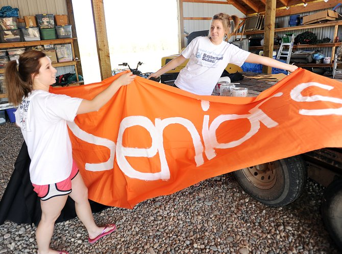 Hayden seniors Jarah Woodley, left, and Rachael Koehler move a banner they helped paint Sunday while decorating their class' float for the 1 p.m. Friday homecoming parade in Hayden. A week of activities will be capped off starting with the parade Friday while the varsity volleyball team - Woodley and Koehler are members - will play at 6 p.m., and the football team plays at 7:30.