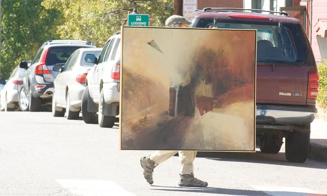 Dale Morris carries a large painting across Ninth Street on Monday. Morris and several other local artists showed up to help the Center for Visual Arts move from its old location on Ninth Street to a new location on Lincoln Avenue.