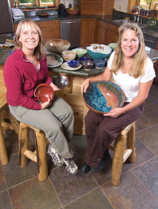 Gail Holthausen, left, and Kathy Thayer display just a few of the handmade ceramic bowls created for the eighth annual Soup Bowl Supper.