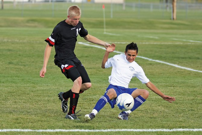 Moffat county high school soccer defender Erik Silva, right, slides to stop an Eagle Valley High School attacker en route to the goal during Tuesday's game at Loudy-Simpson Park. The Bulldog defenders had their work cut out for them as the Devils won the game, 12-0.