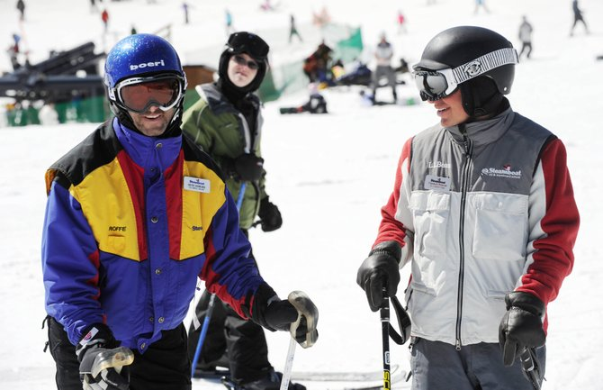 Steamboat Springs Special Olympians, from left, Seth Sobeski and Scott Bjorgum and ski instructor Charley Phelan ski in March at Steamboat Ski Area. This year, Intrawest will recommend all skiers and snowboarders wear helmets at its resorts.