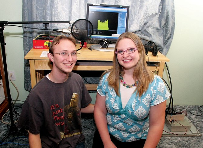 Ricky and Katie Ratzlaff sit in front of their radio transmitting equipment, consisting of a 2-by-2-foot electronic platform, coaxial cable, home computer, rarely-used microphone, and antenna. The setup, minus the microphone and the computer they already had, cost about $800. The experience of owning and operating a radio station is a reminder that people can realize their aspirations if they want, the couple said.
