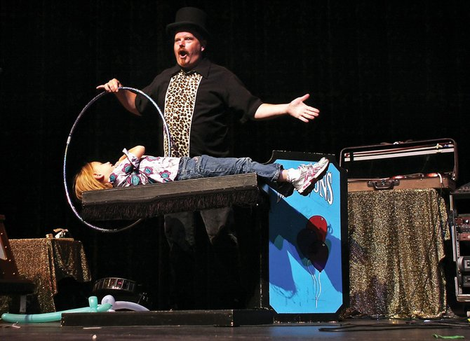 Magician Lanny Kibby makes Alexa Neton, a 6-year-old girl from Craig, hover during a magic show Saturday night at the Moffat County High School auditorium.  The show featured magic acts, tips, dancing and music.