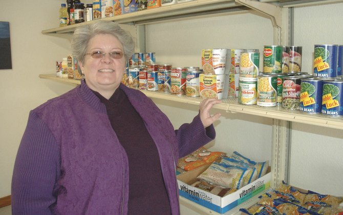 The new site for the LIFT-UP food bank in Hayden includes far more shelf space and square footage than the previous spot. Volunteer Holly Blake, displaying the wares Thursday, handled much of the move and will run the food bank.