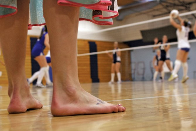 Brianna Montgomery-Braun, Moffat County High School head volleyball coach, coaches her team from the sideline barefoot Thursday night against Rifle during the homecoming game. Montgomery-Braun said she has never worn shoes or socks during her coaching career.