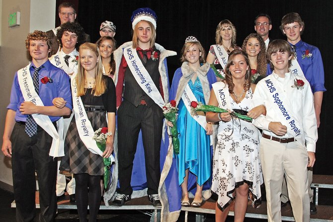 Class attendants, honored faculty and alumni surround the Moffat County High School 2009 homecoming king and queen, Matt Herschberg and Kelsey Grinstead, after a coronation ceremony Thursday in the high school auditorium.