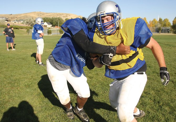 Casey Martin, left, and Drake Mullen work on dominating the trenches during linemen drills at Tuesday's practice. The football team will look to improve its record to 4-2 tonight against Eagle Valley High School.