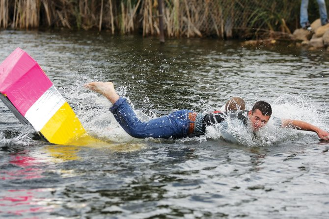 Andrew Raftopoulos takes a dive into the fishing pond at Loudy-Simpson Park on Friday afternoon during the Great Cardboard Boat Regatta. Raftopoulos' boat, shaped as a pencil, could not stay afloat in the cold, choppy water.