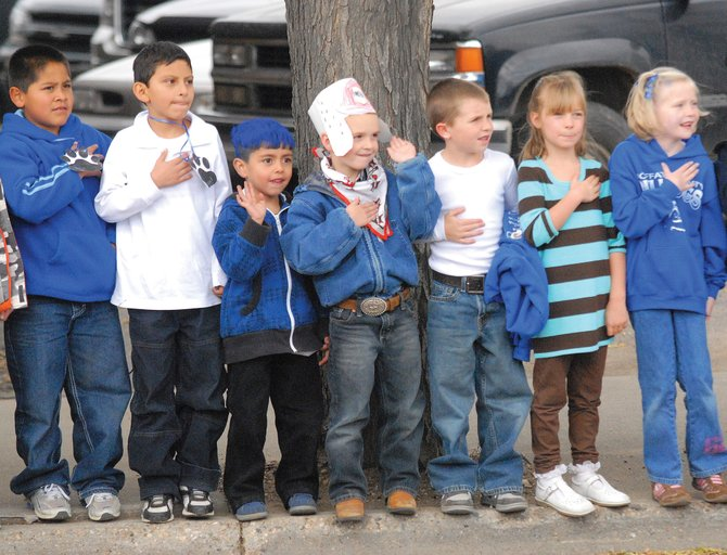 Children from Mrs. Haddock's second grade and Ms. Cookston's kindergarten classes from Sandrock Elementary School watch as the American Legion float comes by with the United States Flag during Friday's 2009 homecoming parade.