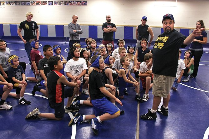 Coach Billy Bingham discusses the rules Tuesday night during the Craig Bad Dog youth wrestling team's first practice. The team's first meet in Oct. 24 at Eagle Valley.