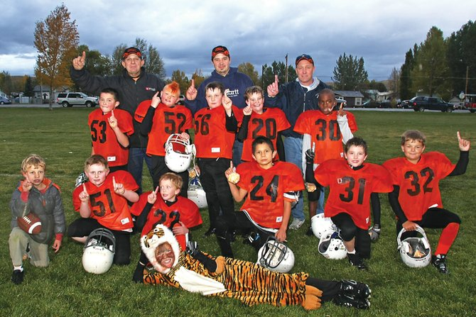 Members and coaches of the Bengals third- and fourth-grade Doak Walker football team pose Wednesday after winning the championship game against the 49ers, 18-0.  The team is, back row, from left, coaches Stanley Peroulis, Calvin Murphy and Jeff Pleasant; middle row, from left, is Elias Peroulis, Zane Shipman, Cody Pleasant, Brayden Tuttle and Gary Warrior; front row, from left, is Luke Pleasant, Jared Baker, Trenton Hillewaert, Alex Nevarez, Connor Murphy and Brady Archuleta. The mascot in front is Cole Hoth.