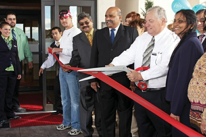 Ed Callison cuts the ribbon at Wednesday afternoon's grand opening of the Hampton Inn & Suites in Craig. The hotel, on Cedar Court, opened to guests Wednesday night.