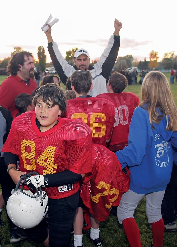 Trey Gallegos turns to the fans on the sideline while his dad, head coach Justin Gallegos, stretches his arms into the air to celebrate the Cardinals' 26-21 victory against the Steelers during Thursday's Craig Parks and Recreation Doak Walker Football fifth- and sixth-grade championship game. The Cardinals won with 40 seconds left on a trick play.