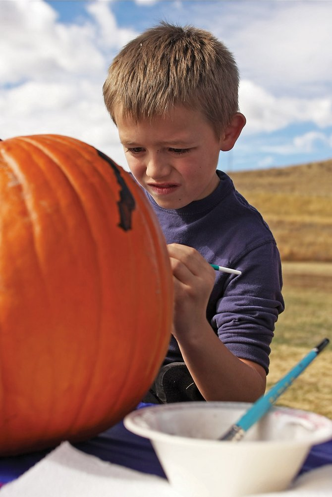 J.T. Rule, 8, paints a pumpkin Friday afternoon at the Wyman Museum. J.T. was part of a Boys & Girls Club of Craig field trip to make scarecrows, paint pumpkins, play in the hay maze and take train rides at the museum during a day of their fall break.