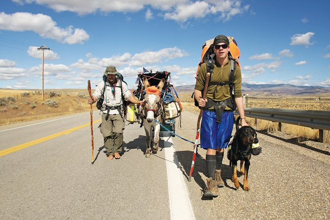 Eric Sheets, left, and Nick Jenkins set out on Colorado Highway 13 toward Craig with their donkey, Moses, and dog, Buck, after fixing a flat tire on their cart. The pair is walking to Seattle to raise awareness for their proposed education program as well as spread positivity and joy.