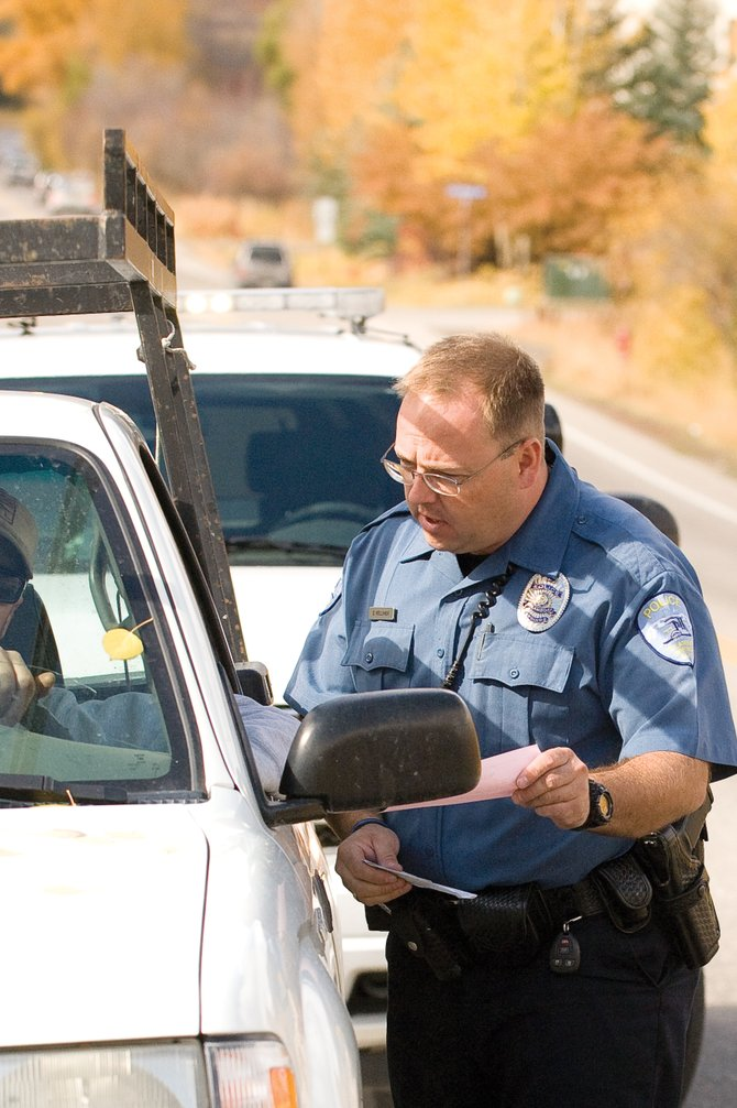 Steamboat Springs Police Officer Dan Kelliher talks to a motorist after issuing a warning ticket at Walton Creek Road and U.S. Highway 40.