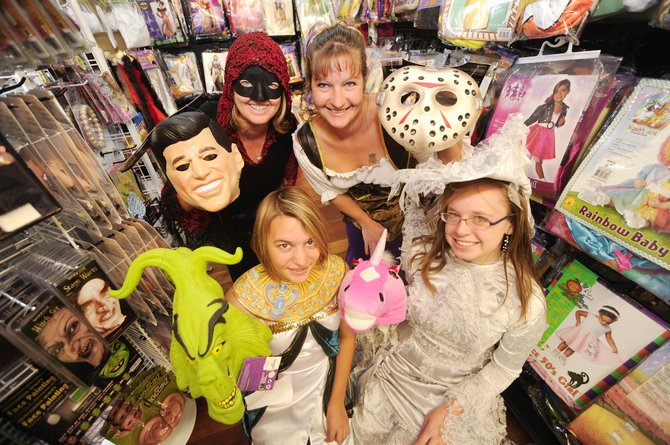 The Costume Party and Dance Shop owner Sandy Pugh, clockwise from top left, Carol Herman, Sara Pugh and Victoria Belz model costumes at the store between 11th and 12th streets on Lincoln Avenue. Pugh said the store would be open through November.