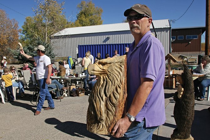 David Van Wagner holds a wooden eagle sculpture during the Auction to Benefit Cory Pike on Saturday afternoon at the OP Bar & Grill. Community members donated the items to raise money for medical expenses accumulating as a result of Pike's battle against lymphoma.