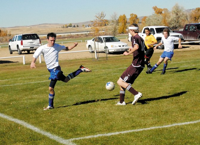 Moffat County's Dustin Carlson, left, completes a no-look pass to Nick Glispy, far right. The boys varsity soccer team defeated Palisade High School, 11-2, on Saturday at Loudy-Simpson Park.