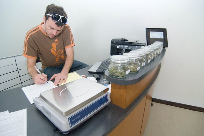 Ryan Fisher, co-owner of Rocky Mountain Remedies medical marijuana dispensary, fills out some paperwork in the business's new location in 2700 block of Downhill Plaza earlier this year. The federal government announced Monday that it will not prosecute medical marijuana users or dispensaries as long as they comply with state law.