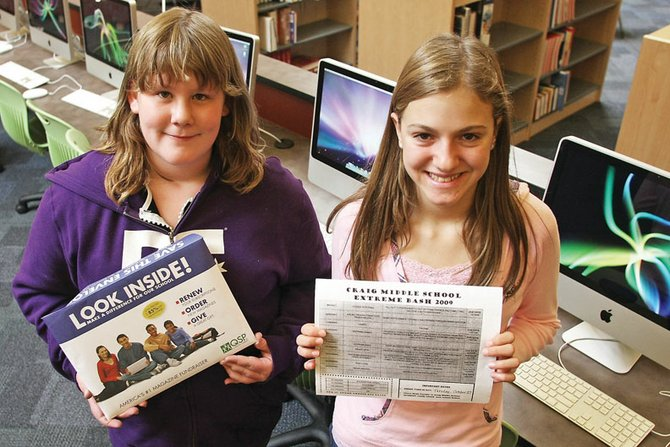 Veronica Mead, left, and Katelyn Peroulis hold up their fundraising packets Friday at the Craig Middle School library. Students at the school are selling magazine packages to fund efforts to bring more computers and technology into the learning environment.
