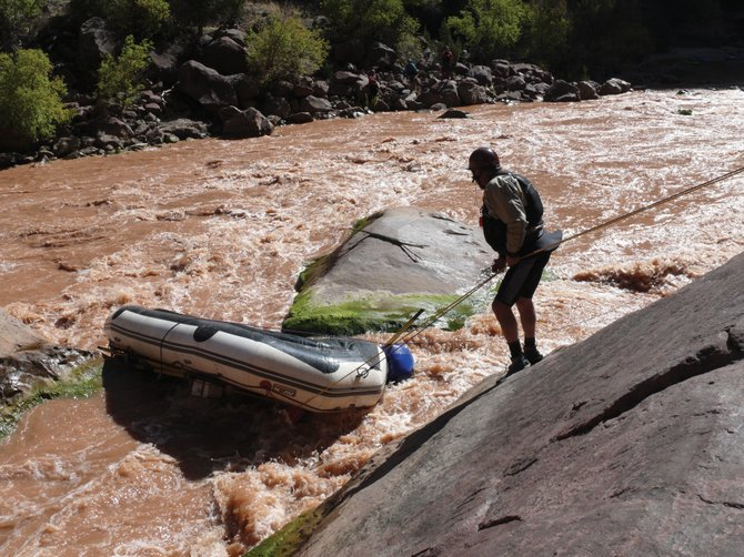 Lowell Whiteman School kayak trip leader Jim Linville assesses how to remove the upturned raft out from between two boulders at the Gates of Lodore on the Green River through Dinosaur National Monument.
