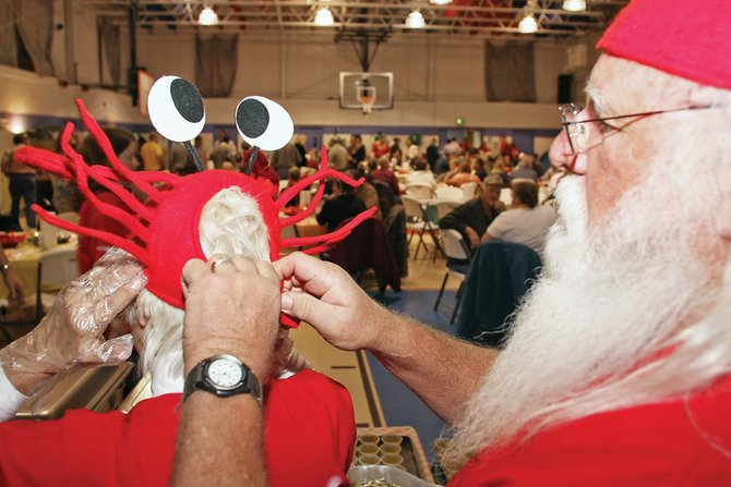 George Kidder, right, helps his wife, Ann, put on her crab hat before serving food and cracking king crab legs Saturday night at Crabfest 2009 at the Boys & Girls Club of Craig. The event included comedian Troy Baxley, a standup comic from Denver, and both live and silent auctions to benefit the Craig Chamber of Commerce.