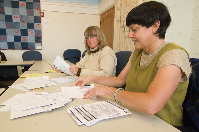 Catherine Carson, front, and Judy Birmingham prepare mail-in ballots for counting Monday at the Routt County Courthouse in Steamboat Springs. County Clerk & Recorder Kay Weinland said as of Monday, the county had received 1,675 verified ballots out of more than 13,400 sent to voters.