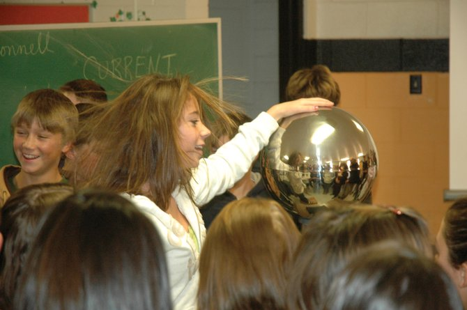 Eighth-grader Neylan Wheat participates in a demonstration last week to demonstrate how static electricity works by placing her hand on a Van de Graaff generator. The science experiment was one of several presented by John McConnell, founder of the Western Colorado Math and Science Center in Grand Junction.
