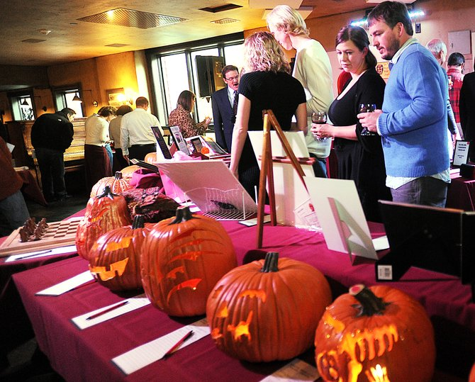 Chris Roberts, right, and Katie Stockhaus browse the auction items available Sunday afternoon at the Lowell Whiteman Primary School's Scholarship Auction at the Ghost Ranch Saloon in downtown Steamboat Springs. The pumpkins were designed by 11 local artists to coincide with the Halloween theme of the auction. The proceeds from the highest-bid pumpkin will be given to LIFT-UP of Routt County.
