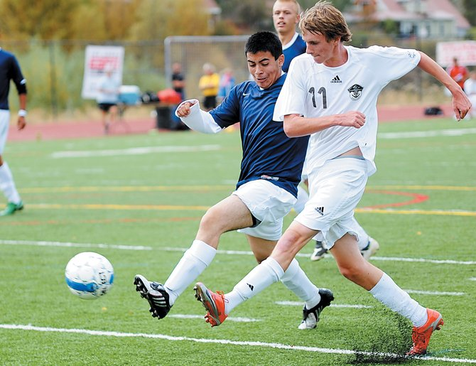 Steamboat's Evan DePuy, right, blasts a shot past a Rifle defender in an 11-0 win earlier this season in Steamboat Springs. The Sailors hope to have the same kind of home result Tuesday as they battle D'Evelyn in the first round of the Class 4A soccer playoffs.