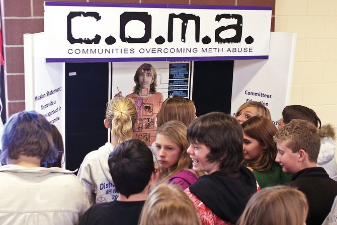 Craig Middle School students surround the Communities Overcoming Meth Abuse booth Wednesday at the school's cafeteria. The booth was used to educate young adults about the dangers of methamphetamine abuse and the drastic physical effects the drug can have.