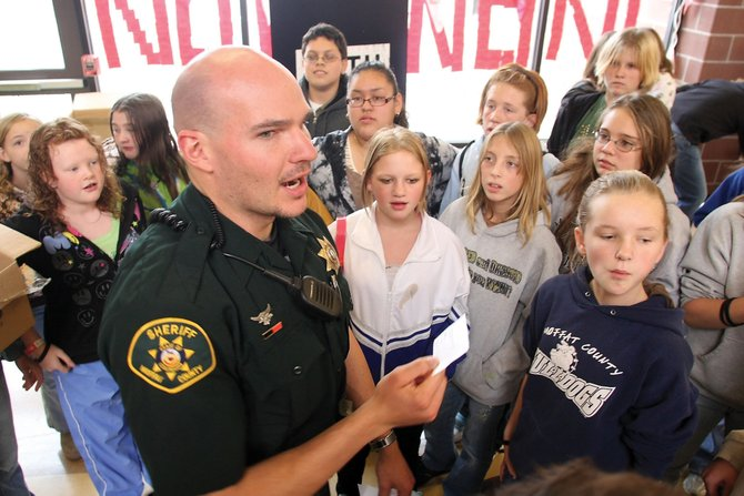 "Ryan Hess, a Moffat County Sheriff's Office deputy, reads off a raffle ticket for COMA gear Wednesday during seventh-grade lunch at Craig Middle School. Hess appeared at the school as part of ""Not Even Once"" Week, an educational, anti-meth awareness campaign."