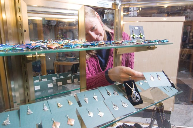 Store employee Jill Bergman pulls a pair of earrings from one of several display cabinets at the Artisans Market. Store owner Jan Lomas said that after consistent shoplifting programs, she invested more than $10,000 in glass cases to secure easily concealable objects - but the cases can make shoppers less likely to buy, Lomas said.