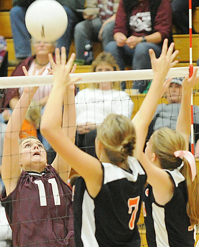 Soroco's Brittany Shaffer tries to tap the ball over a pair of Hayden defenders last week. The Rams and the Tigers will compete starting today in the district volleyball tournament in Meeker.